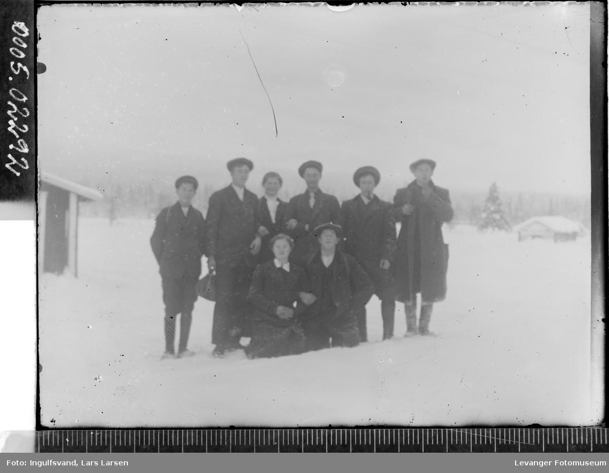 Gruppebilde av åtte ungdommer i vinterlandskap.