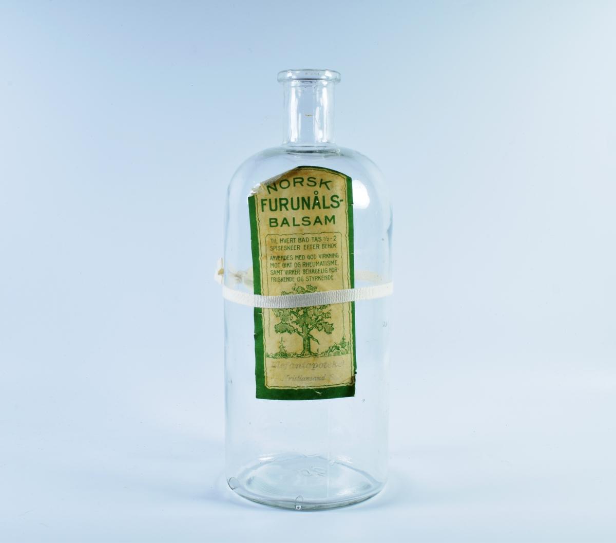 Fire flasker i klart glass.  a-b: Glassflasker med papirkork.  c: Glassflaske uten kork. Gulnet etikett med grønn ramme og motiv av et furtre.  d: Mangekantet glassflaske med sort plastkork.