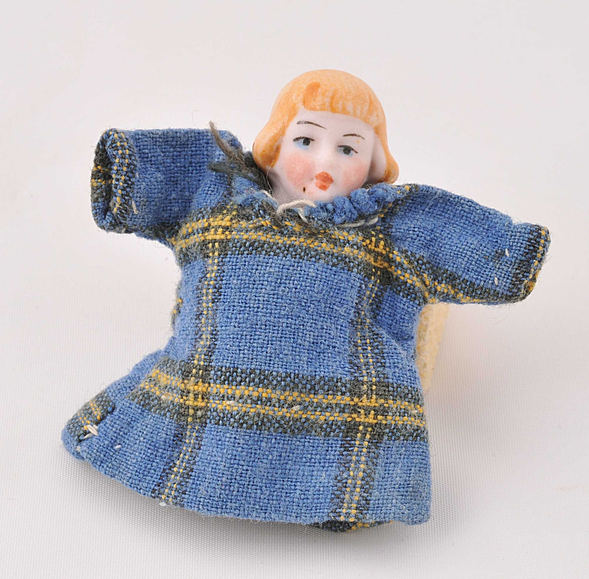 Lita porselensdokke uten armer og bein. Kledd i blårutete bomullskjole.