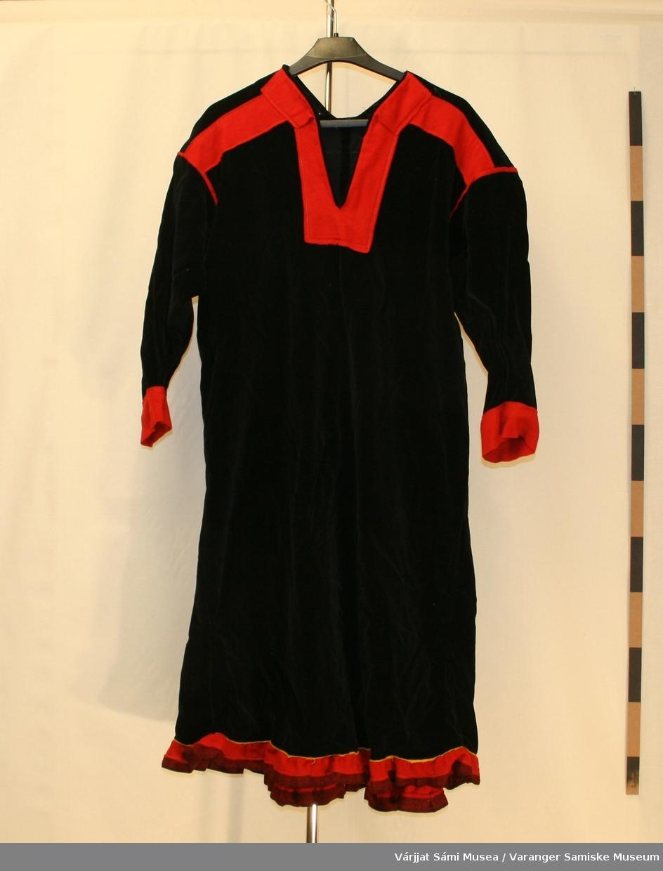 Damekofte av svart fløyel.. Kofta er veldig vid. 3 røde striper på ryggen. Rødt klede på armene. Holbien lik polmakkoften, en jarekant