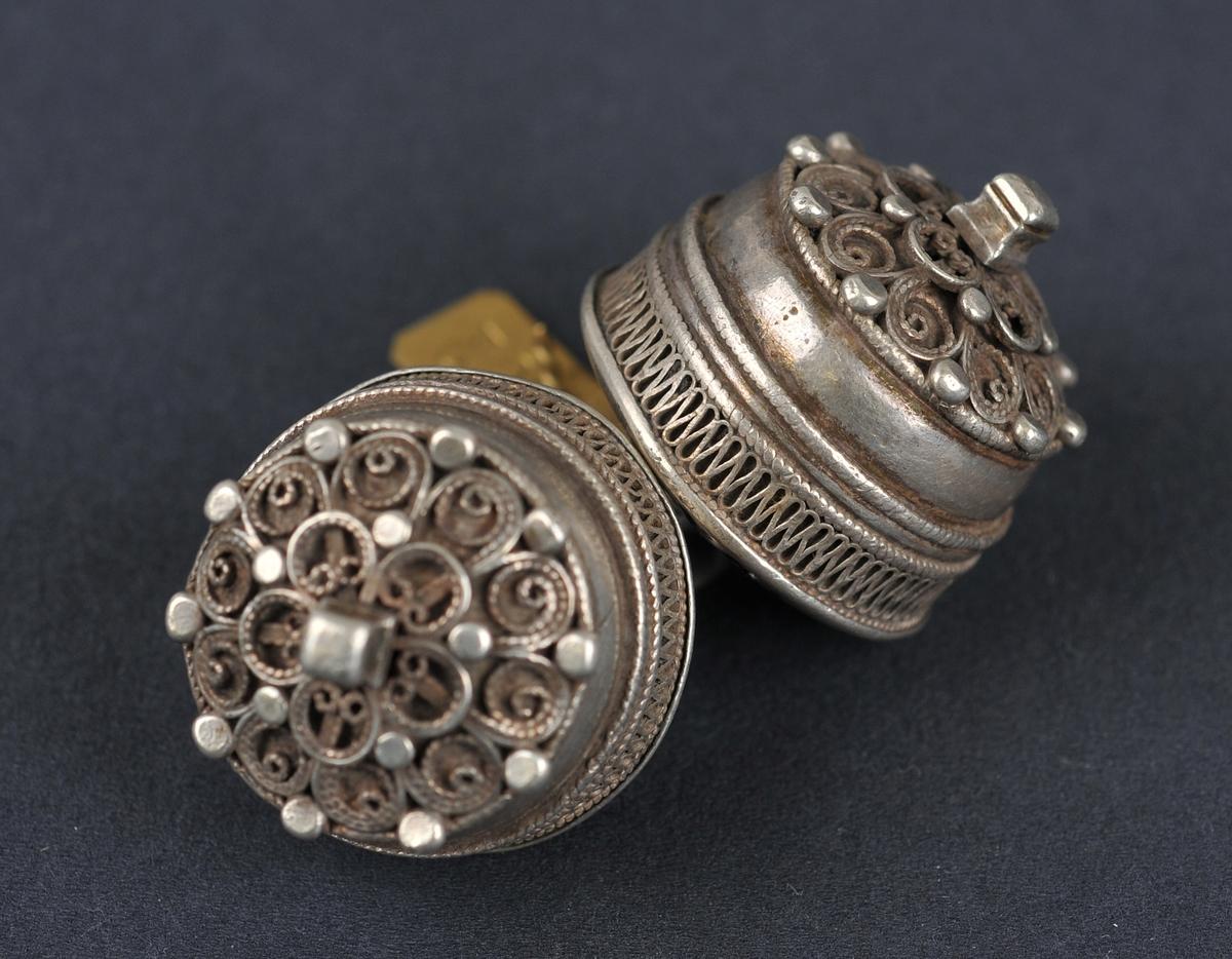 To knappar som er hekta saman med ein liten ring. Knappane har 10-dela filigransroser med 5-dela roser oppå. Kolteknapp.