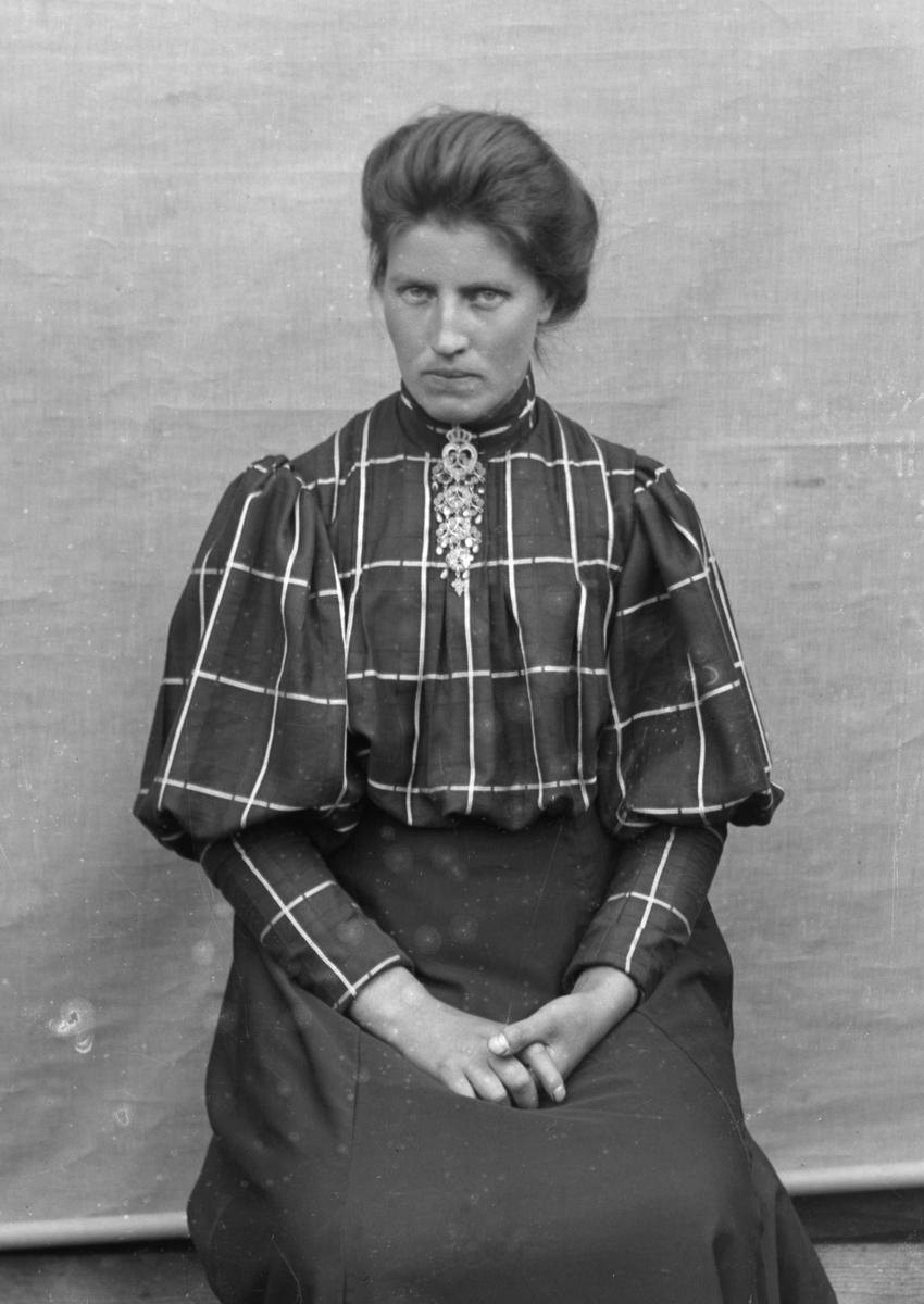 Kvinne sittende foran hvitt lerret, kledd i rutete bluse og mørkt skjørt.