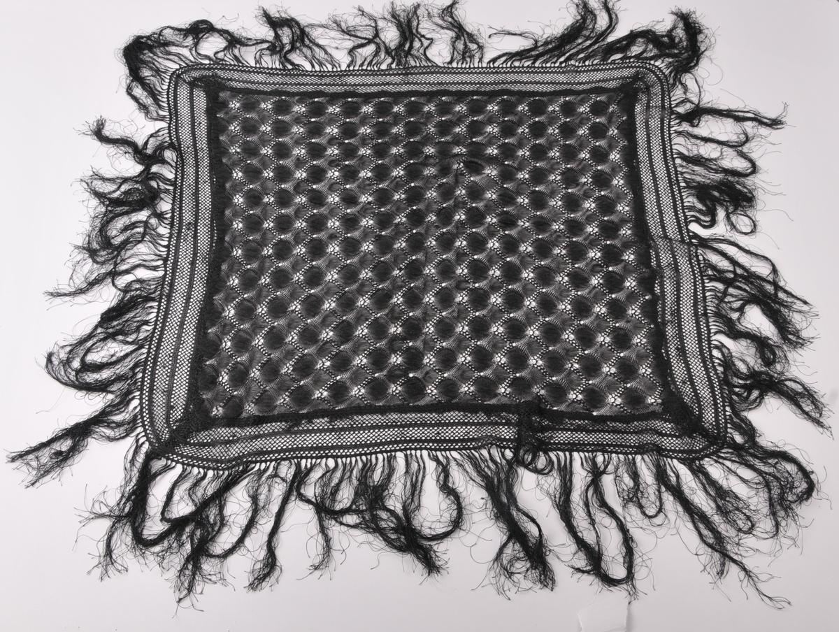 Svart maskinstrikka silkesjal med knytte frynser langs alle sider.