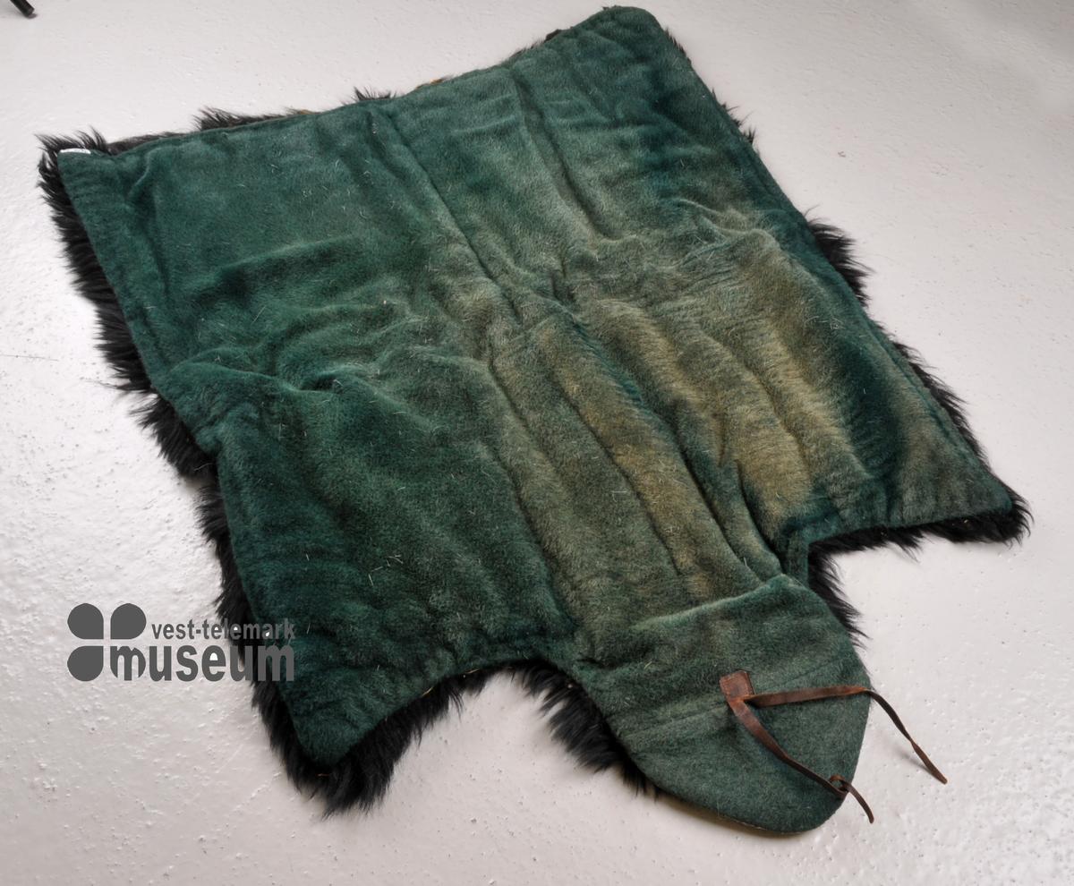 Bjørnefell, vattert med ull og strie. Foret er flossa ull. Hovudimitasjon i eine enden, laga av raud filt og kvitt skinn. Fellen er mykje øydelagt.