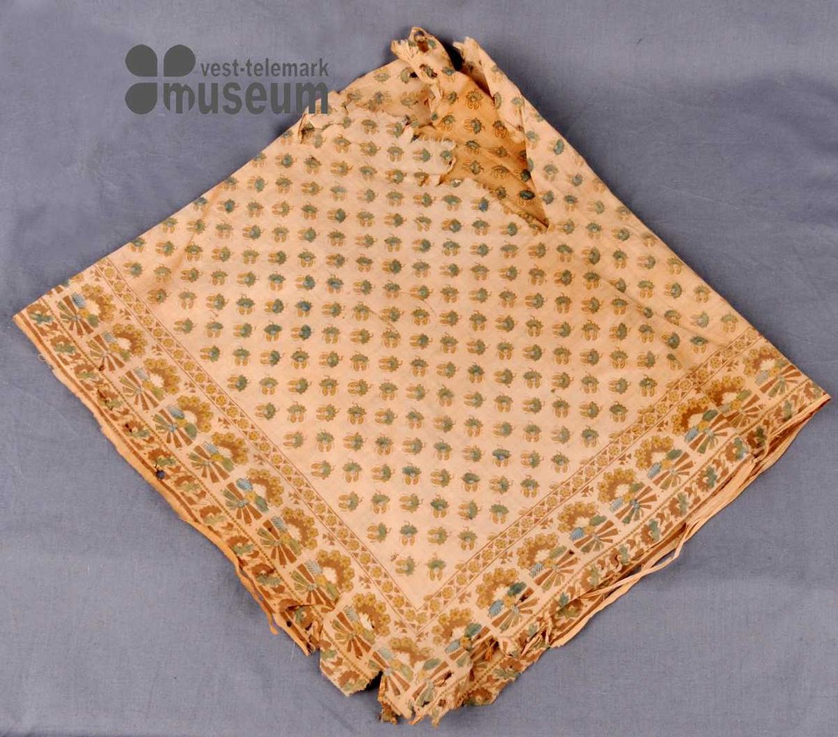 Kvadratisk bomullstørkle med trykt mønster. Langs alle fire sidene er det ein bord med rader av stiliserte blomar.  Over resten av tørkleet er det  jamn fordeleing av like store blomar i rader.  Kan ha vore bruka som  bringeklut eller ruddeplagg.
