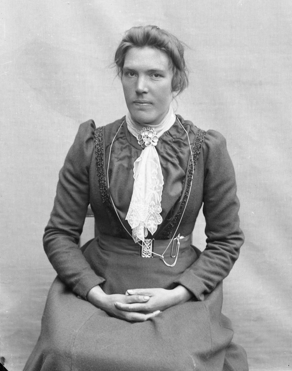 Kvinne kledd i mørk kjole med kalvekryss og sølje, sittende foran lerret