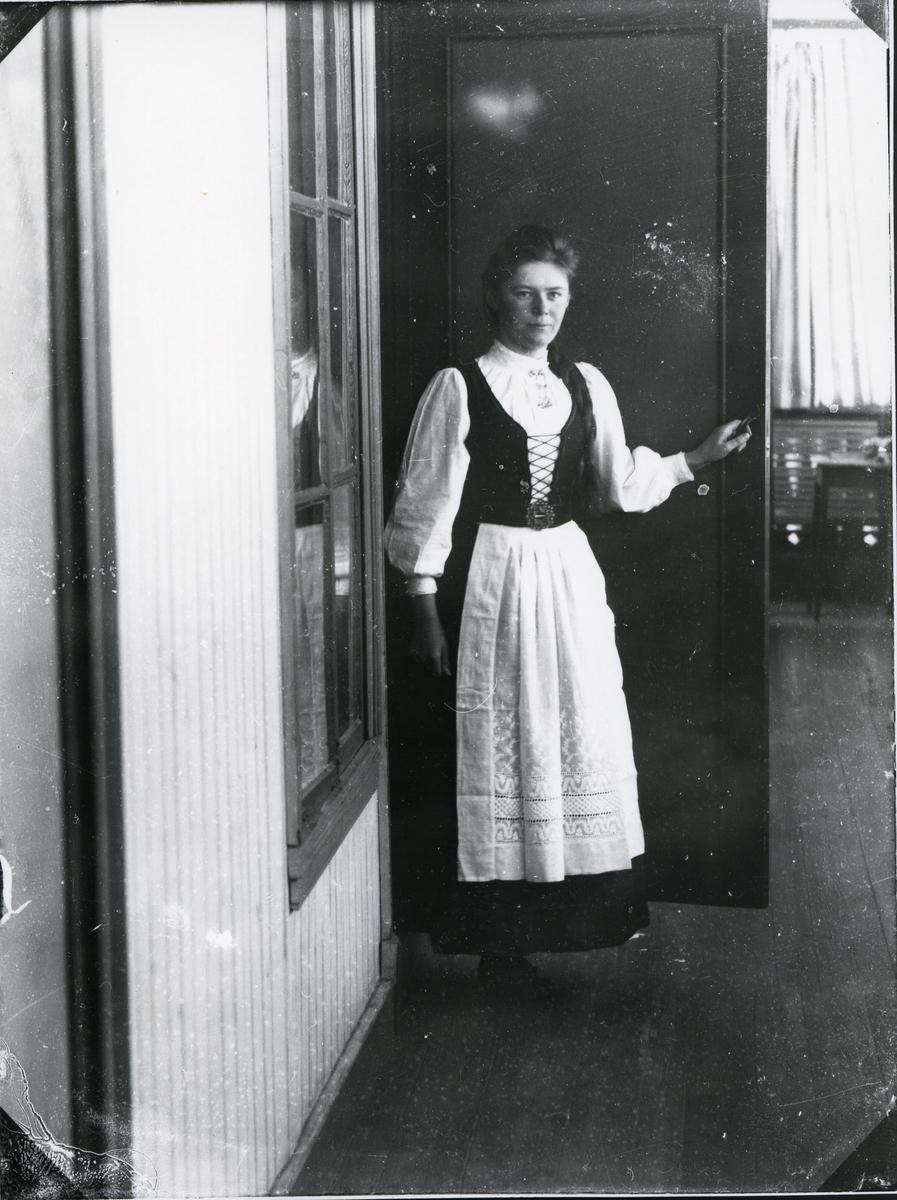 """Kvinne kledd i bunad/""""nasjonaldrakt"""", stående i døråpning, antagelig ved hotell e.l."""