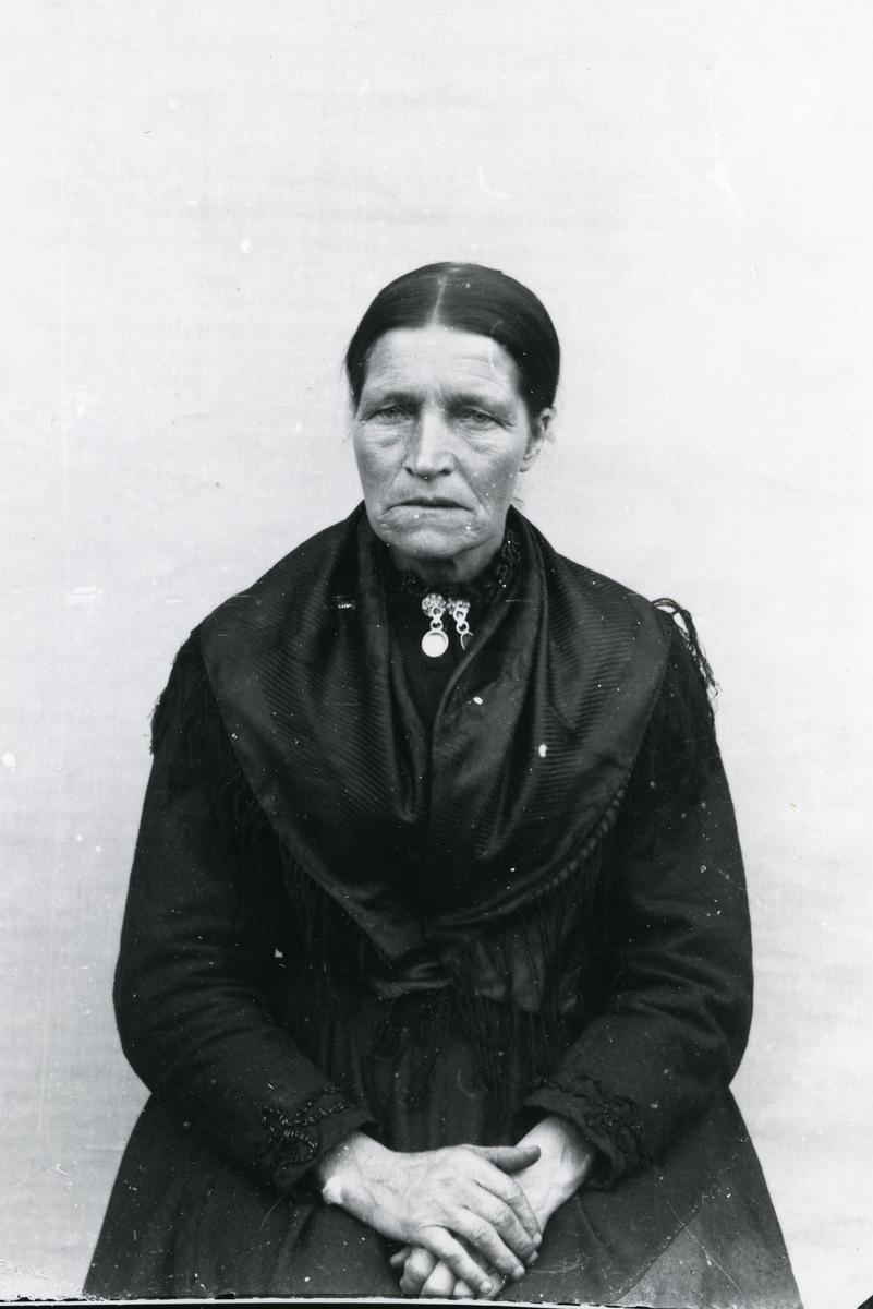 Mørkkledd kvinne i halvfigur, med sølje og silkesjal, sittende foran lerret