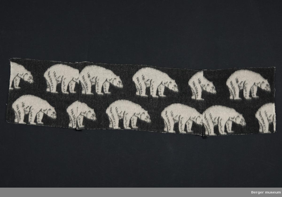 Hvit isbjørn på svart bunn. Her er det tre deler som er sydd sammen. Antagelig er det en reklamasjon på stoffet da det ikke er skikkelig ruet. Feil etterbehandling da varpen (renningen) synes.