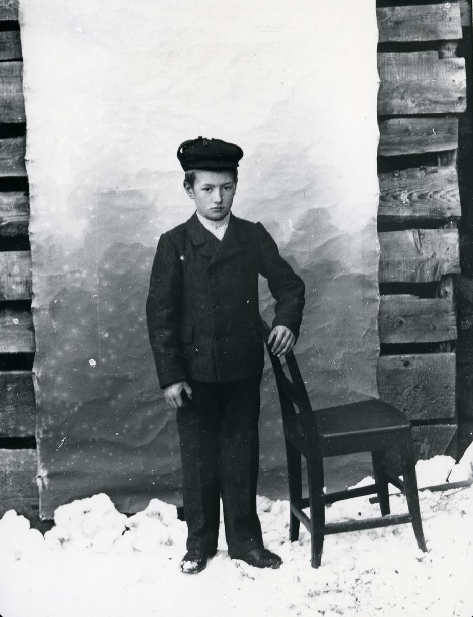 Dresskledd gutt med lue, ved stol, lerretbakgrunn