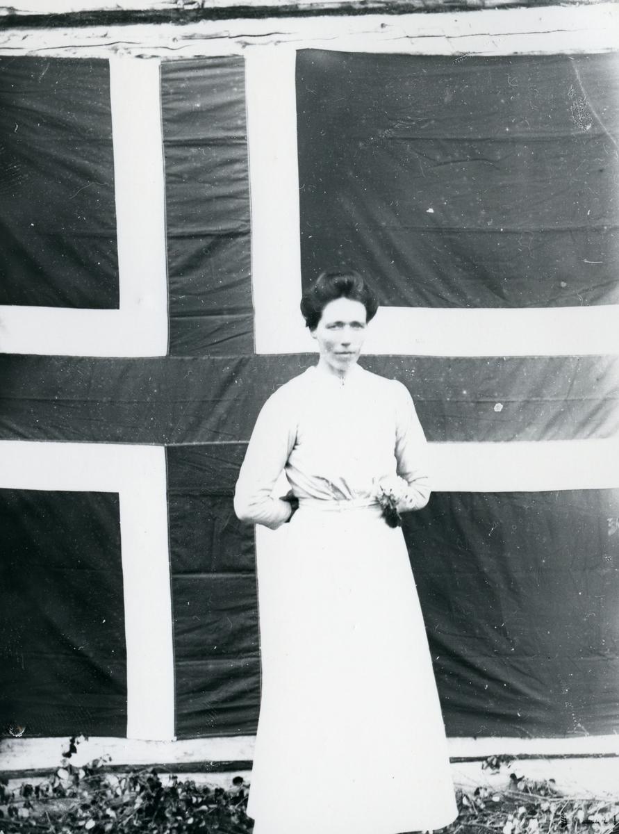 Kvinne i helfigur, stående foran norsk flagg som lerret