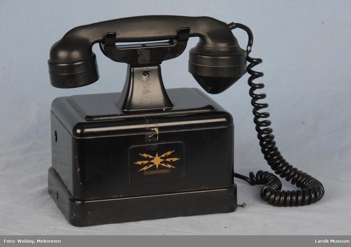 Telefonapparat uten tallskive. Røret ligger i en gaffel.