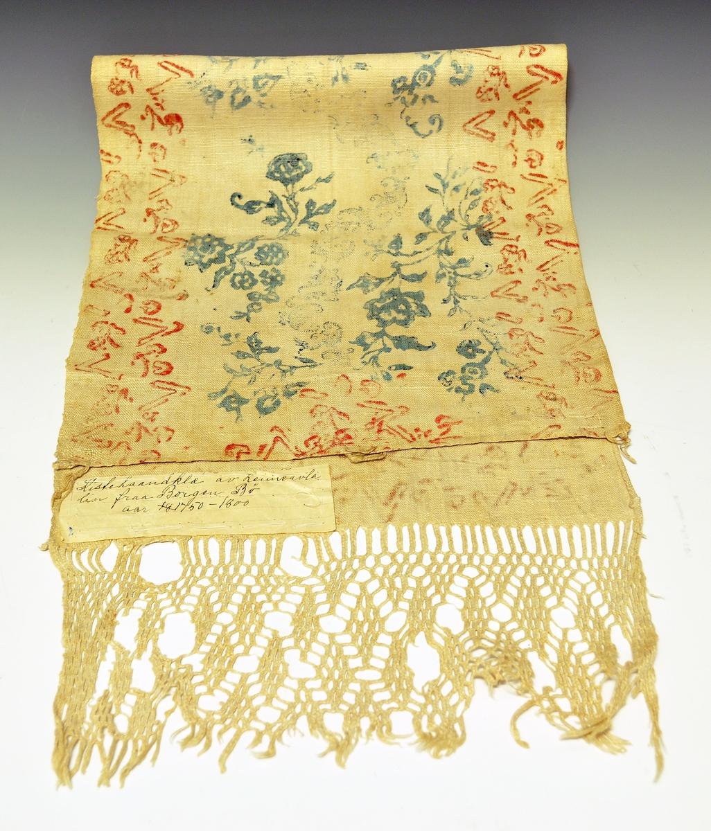 """Rektangulær tekstil med firefletting i den ene enden, samt mønstertrykk i blått og rødt over hele flaten. Tekstilen har jarekant langs den ene langsiden, og en smal innsydd kant på den andre. Øverst opp er det også en smal kant og tre påsydde hemper. Tekstilen avsluttes med at renningen er fireflettet. Tøyet er av lin og er antakeligvis """"heimelin""""."""
