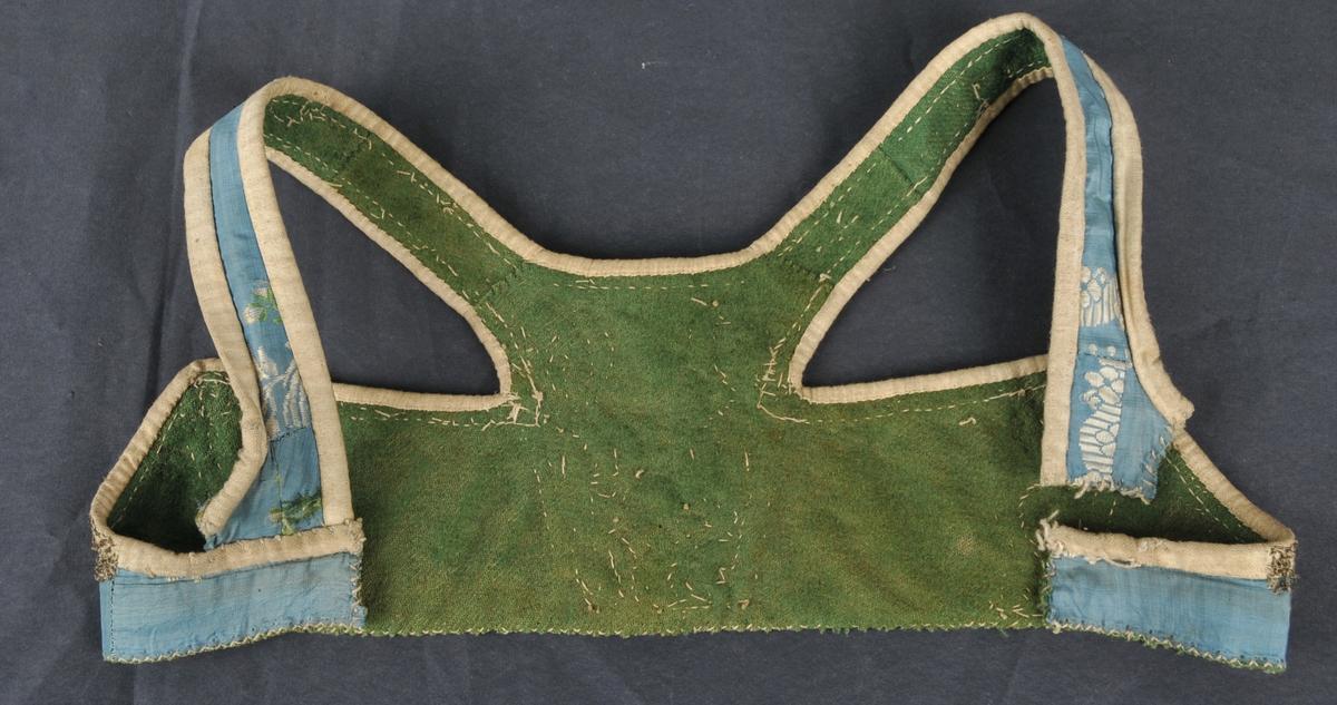 Liv med spissar i ryggen og selar som går heilt ned framme. Ytterstoff av brosjert silkestoff. Mønsteret i dei to ryggstykka er ikkje symetrisk. Livet har saum midt i ryggen. Fôra med grønt kypervevd ullstoff.    Sylvkniplingar i to ulike bredder som dekor ned frå og over spissane i ryggen, ned midt bak, rundt halsringing bak og eit stykke nedover langs båe sider av selane. Kniplingane er sydd på gjennon både ytterstoff og fôr.  Livet er kanta med kvitt toskaftvove bomull. I nedre kant er for og ytterstoff kasta over, samla.  Selane er klipt av nede ved sidestykket. Den eine selen er laus medan den andre er sydd på slik at nedrekanten dermed får kortare lengde. Handsydd med kastesting, forsting og attersting med lintråd.
