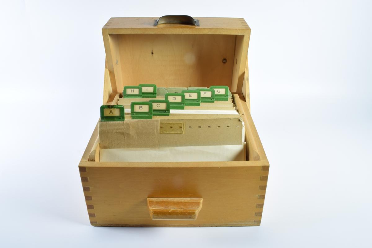 """Farmakologisk kjemisk kartotek i arkivboks av tre. I arkivboksen ligger også et tynt hefte med tittelen """"Vejledning i identitetskontrol i apoteket"""" af H. Thomsen, K. Ilver og F. Reimers. 2 udgave, Utgivet af Danmarsk Apotekerforening, 1967."""