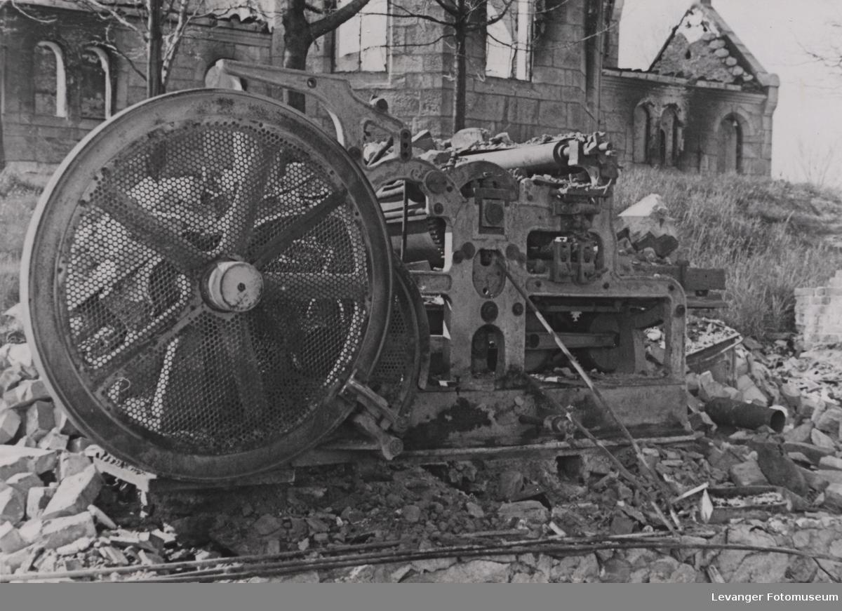 Ødelagt trykkerimaskin med ruinene av Steinkjer kirke i bakgrunnen, etter bombingen.