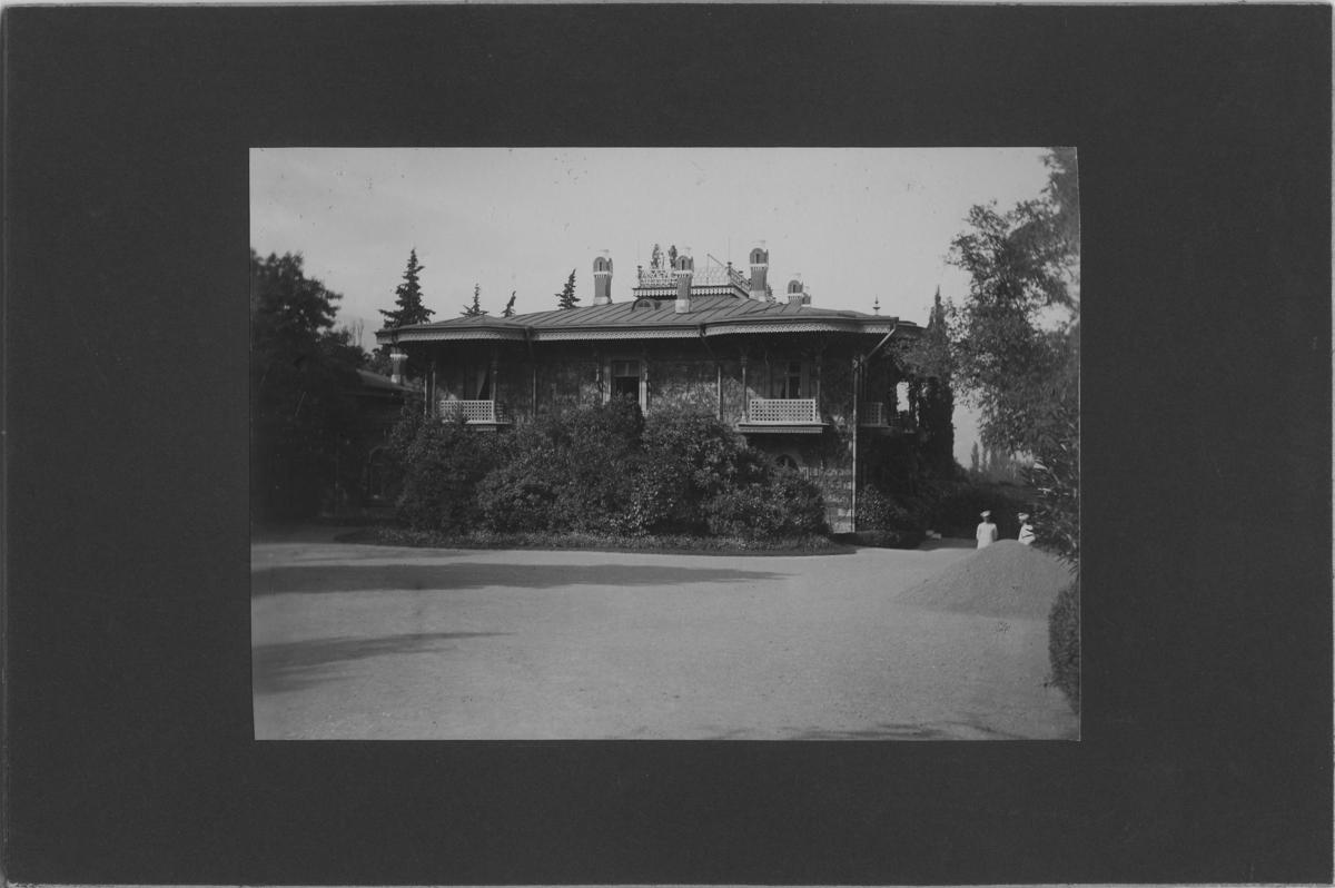 'Vy med hus med omgivande träd och buskar. 2 personer stående en bit ifrån. ::  :: Se serie med fotonr. 5271:1-15. Serie fotonr 5269-5292, Stuxbergs resa till Kaukasien, 1897.'