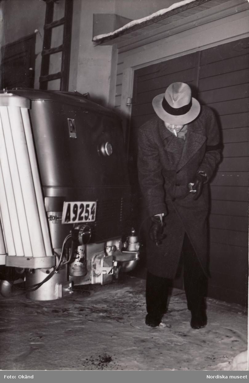 General Motors Nordiska Ab. Prins Bertil kontrollerar gengasen med en tändsticka. Han kör en gengasdriven Chevrolet
