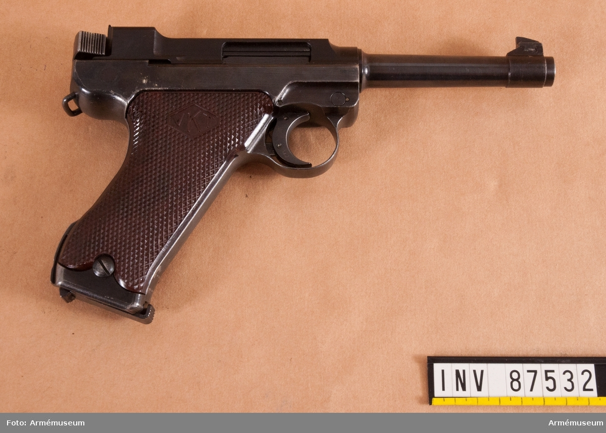 Pistol med tillbehör och insruktionsbok i schatull av ljust trä.