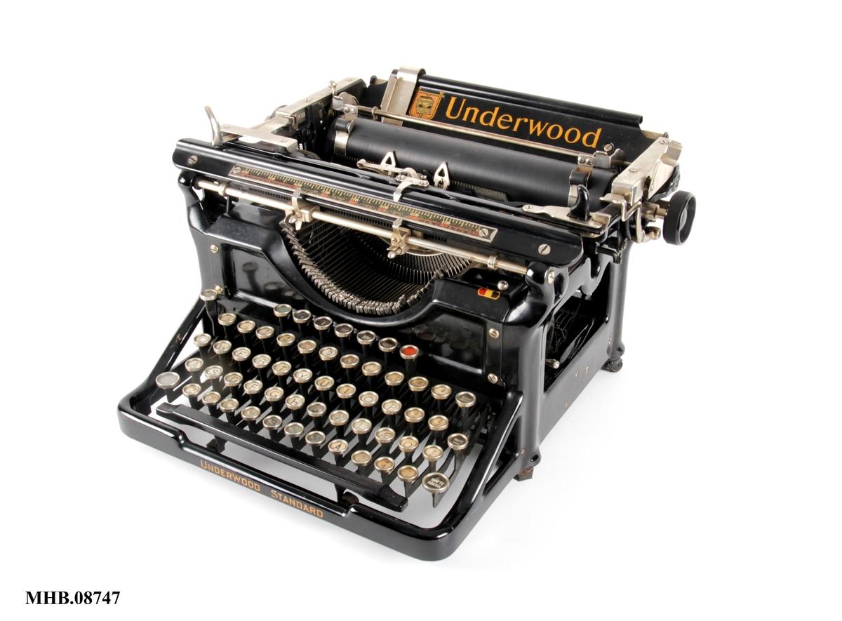 Skrivemaskin med runde taster og valse nedfelt i bakkant.