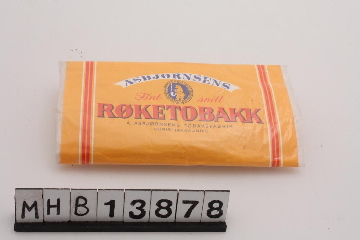 Emballasje for rulletobakk med rektangulær form. Den består av plastbelagt papir som danner en beholder for tobakk med lokk over.