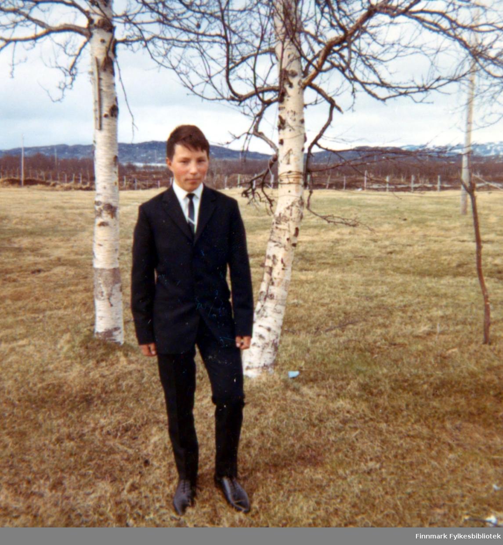 Konfirmanten Torbjørn Nymo poserer for fotografen iført en mørk dress. Sted er ukjent, men kan være i Ildskog i Porsanger.