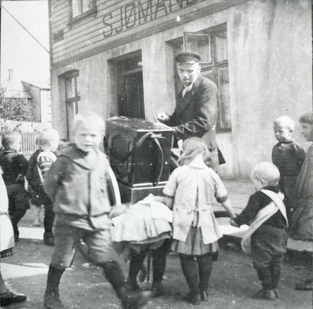 Lire-Teodor med lirekasse. Flere barn rundt ham. På husveggen bak ham står: Sjømand......