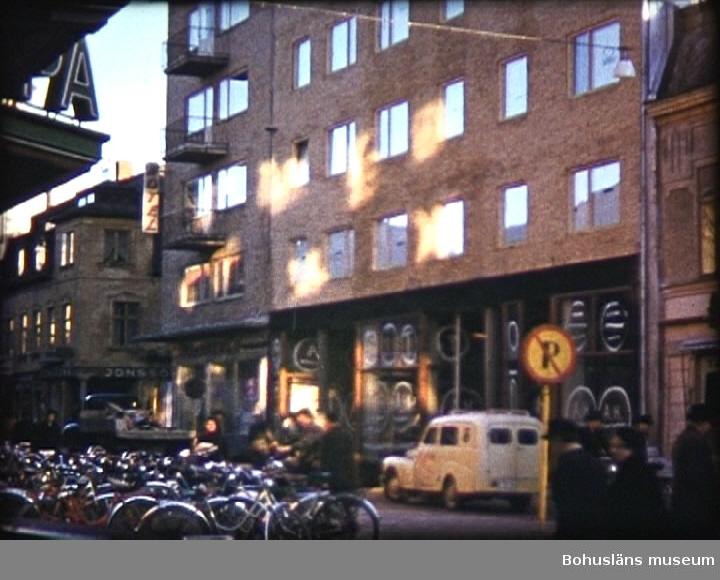 """1) Stadens nya kallförråd. 0003 T.v. Uddevalla Stads nybyggda kallförråd vid Södra Hamnen samt järnvägsspåren till Juno-Hus. t.h. """"Gula Magasinet"""" disponerat av Grosshandelsfirman Robert Wallström under 30–40-talen.  2) Byggandet av pumpstation, Junogatan. 0005 Stadens nya pumpstation för avlopp från Söderområdet byggd vid Junogatan (numera inbyggd i höghusets källare).  3) 0014 Dåvarande Fiskauktionshallen på Badhuskajens västra ända. Där framför den gamla materialgårdsslipen vid sjösättning av utloppsledningen för avlopp i hamnkanalen. 0034 T.h. kommunalarbetaren Fredrik Bengtsson. 0049 Gästande minsvepare från marinen på väg ut från Bäveån med Norra Kajen (""""Sannes Mage"""") i bakgrunden.  4) Sjösättning på Uddevallavarvet.  Stadsfullmäktiges ledamöter vid studiebesök på Uddevallavarvet. 0100 Fru Clary Thordén och t.h.  Stadsfullmäktiges ordf. Axel V. Johansson (""""Småland""""). 0148 Fru Clary Thordén och t.h.  med hatt stadsfullmäktige-ledamoten Axel-Ivan Andersson.  5) Tennisspel på Kålgårdsberget mellan Börje Fornstedt och Tärneld.  6) Motocross på Kuröd. 0257 Snäckskalsbankarna vid Bräcke Gård. 0308 I bakgrunden synes magasin för förvaring av salt tillhörande """"Riksnämnden för Ekonomiskt Försvar"""" (Magasinet beläget söder om dammen och söder om Kurödsvägen).  7) Vägmålning av Göteborgsvägen vid Bratteröd. 0326 Göteborgsvägen mot norr vid krönet över järnvägsviadukten vid Bratteröd.  8) En sommardag i Skeppsvikens camping. 0354 Skeppsvikens Camping och Kafé.  I kafébyggnadens andra våning bodde på 30-talet badplatsvaktmästaren Herbert Lysell, sedermera bagaremästare vid övre delen av Kungsgatan. 0412 Juno-Hus långa båtvarv på ängen öster om badplatserna i Skeppsviken.  Pråmar och fiskebåtar byggdes för export. 0421 Campingplatsen öster om Flaggberget (Hästepallarna). I bakgrunden ligger Kärra Holme och t.h. Sörviks Udde.   9) Vyer från Hasselbacken, Sörkälleparken och Rådhuset. 0432 Hasselbacken; blomsterarrangemang utmed muren mot Kungstorget (norrut). 0506 Sörkällepark"""