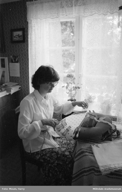 Lindome Hembygdsgille firar 20-årsjubileum på Börjesgården i Hällesåker den 23 juli år 1983. En kvinna knypplar.  För mer information om bilden se under tilläggsinformation.