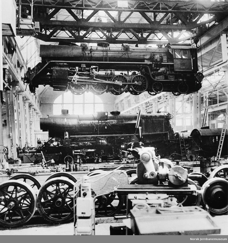 """Verkstedet Marienborg med damplokomotiv type 49c nr. 470 i kranen og en """"stortysker"""" på verkstedgulvet"""