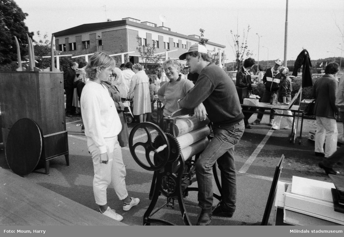 """Lindome Frikyrkoförsamlings ungdomssektion håller sin årliga loppmarknad i Lindome centrum, år 1983. """"Pastor Anders Svensson i samspråk med Carina och Anne Marie Kruber om priset på en mangel modell äldre samt större.""""  För mer information om bilden se under tilläggsinformation."""