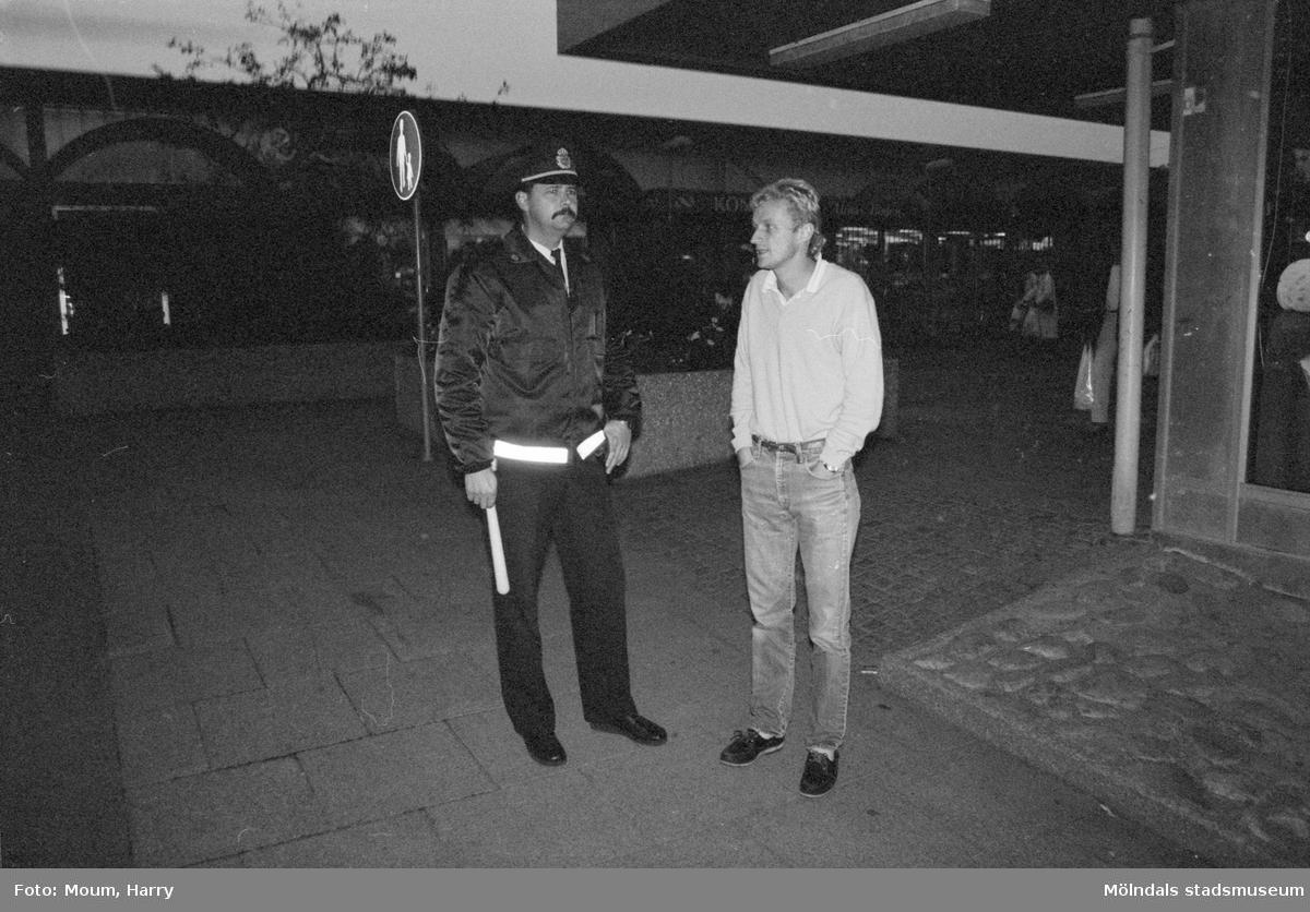 Kvarterspolis Ola Candefors, Batong-Ola kallad, ses tillsammans med en man i Lindome centrum, år 1983.  För mer information om bilden se under tilläggsinformation.