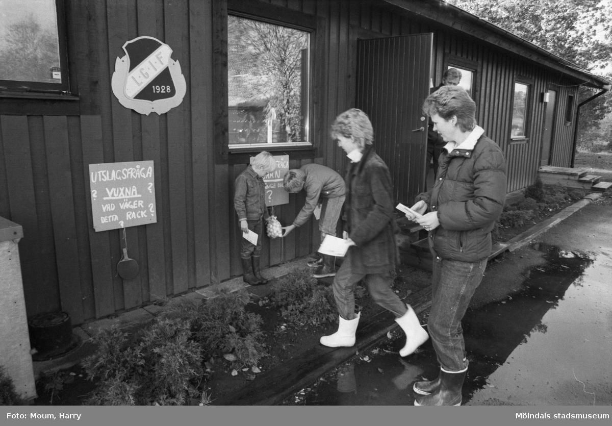 """Lindome GIF BTK anordnar poängpromenaden Bunketorpslunken i Bunketorp, Lindome, år 1983. """"Det gällde att vara försedd med stövlar för att klara den blöta lunken. Här är det Inga-Britt, Fredrik och Martin Alminger som kollar slutfrågan tillsammans med Eva Mari Karlsson.""""  För mer information om bilden se under tilläggsinformation."""