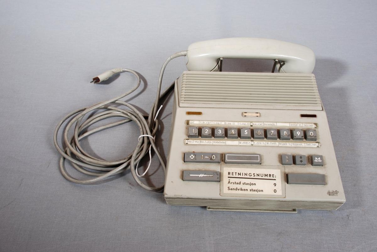 Telefonapparat med sentralfunksjon, høyttalende og med telefonrør. Firkantet form med høyttaler på toppen, telefonrør hengt på i bakkant. 10 taster nummerert fra 1-0. Ulike tastefunksjoner lenger ned på apparatet. Ledning for tilkopling til kontakt