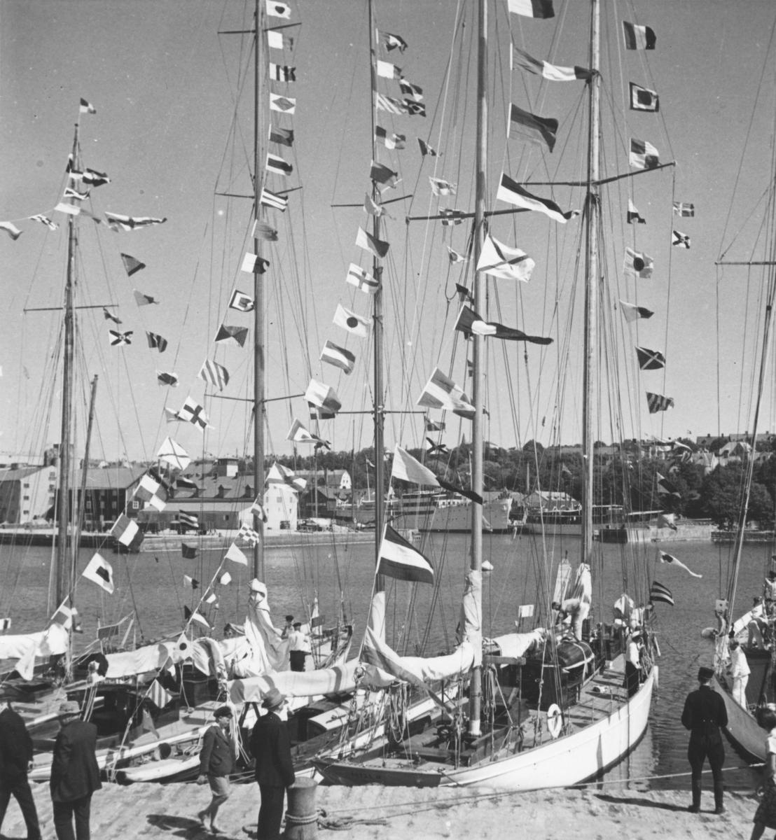 """Fartyg: ETTSI IV                        Byggår: 1923 Varv: Neptun-Werft, Rostock Konstruktör: Barg, Gerhard Övrigt: Namnet ETTSI IV kan tydas med lupp på akterspegeln på den närmaste båten; detta visar att bilden tagits inför Gotland Runt 1937, eftersom ETTSI IV inte deltog då Gotland Runt åter ägde rum 1939. I seglingsprotokollet från 1937 (KSSS årsbok 1938) uppges en H. Kadelbach ha varit """"Ägare eller rorsman"""" till/på ETTSI IV. I bakgrunden t v skymtar Ångfartygs Ab Gotlands fartyg GOTLAND (b. 1936) och HANSA (b. 1899). Jfr Fo134971 från samma tillfälle. Anteckningarna på baksidan tyder på att detta fotografi varit avsett att återges i tryck, men var så skett är inte bekant."""