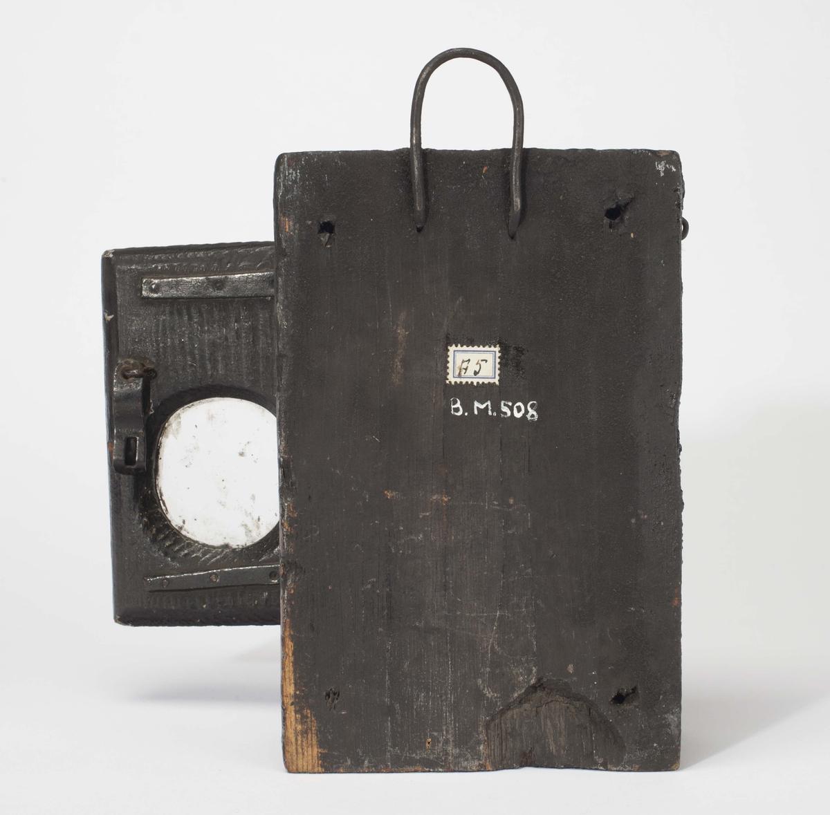 Kasse for oppbevaring av oppholdsuret. Grovt uthula trekloss med oppheng. Hengslet dør med glass.