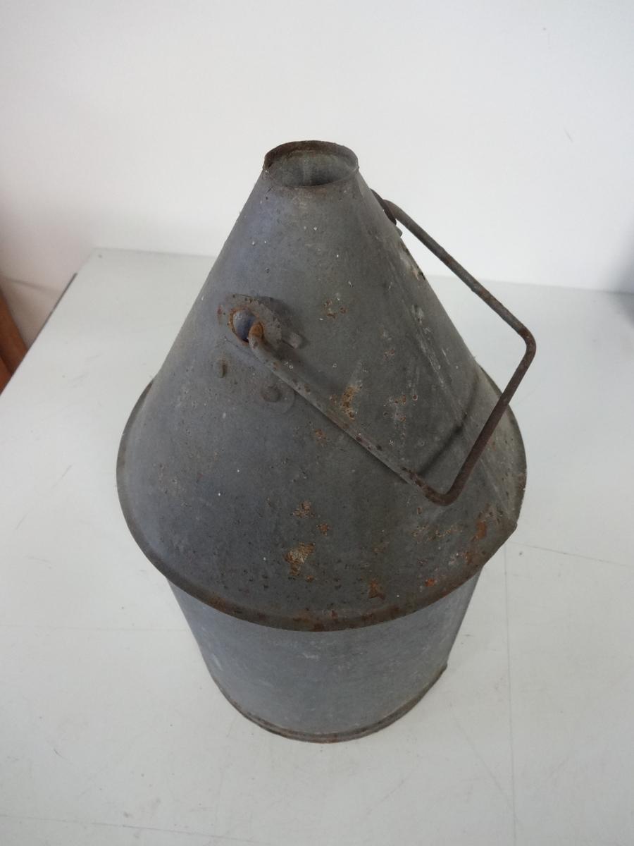 Oljekanne brukt til transport og påfylling av olje/parafin på fyr eller fyrlykter. Kannen har vippehank som håndtak og åpning på toppen. Rund konisk form. Kannen er malt grå.