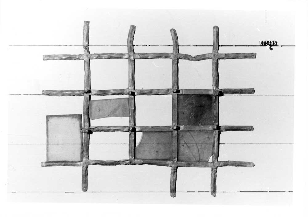 Gitter med rektangulære ruter i uregelmessige former. Blyinnfatning med 5 glasstykker.
