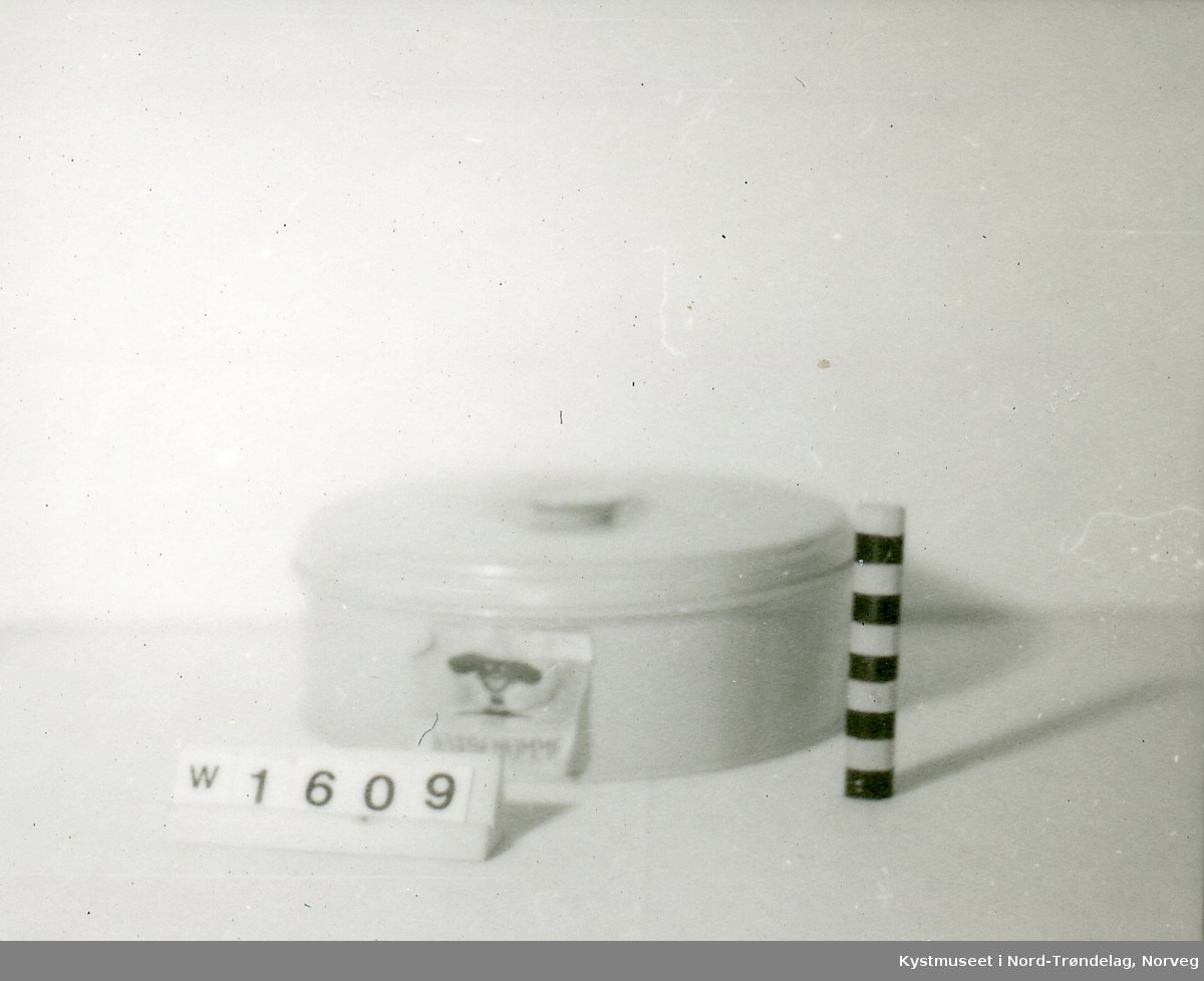 """Form: rund. Blikkboks til oppbevaring av kardemom. Den har en lapp festet på selve boksen, der det står """"malt kardemomme""""."""