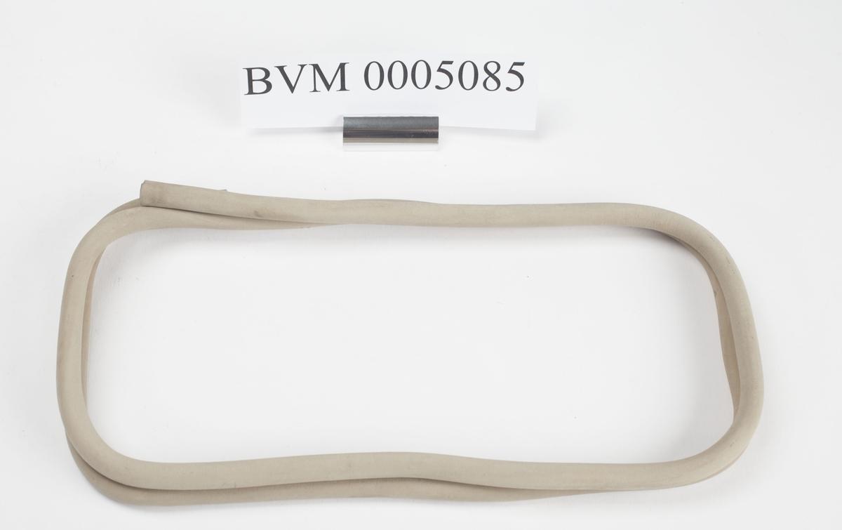 Lys grå gummislange kveilet opp i futteral BVM 5084. Så stiv og sprø at den ikke kan rettes ut uten å gå i stykker.