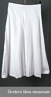 """Vit, bomull, mycket vid kjol med resår i midjan. Längden långt under knät (midi). Kjolen sydd i fyra vådar. Firmamärke: """"GETTI S.P.A.""""Sommar-, vardagsplagg.Anm: fållen skadad"""