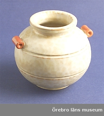Mått, halsring: 7,6 cm.Vas av keramik.Flammig, matt, gulvit glasyr med handtag i orange glasyr.Märkt i botten: EKEBY  71Neg.nr. 436/82