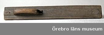 Mangelbräde av ek. Består av en långsmal bräda med profilerade långsidor. Ett böjt handtag är inskjutet i en skåra och en järnspik är islagen i handtagets bakre utskjutande del. Hål för att fästa handtaget med träpluggar har gjorts. Träpluggarna saknas. Handtagets kortsidor är dekorerade med nagelsnitt. På brädets ovansida står: ANO 1722, inom två tvärgående nagelsnittsbårder står KID, uddsnittsdekoration och ett hjärta. Runt ovan nämnda en uddsnittsbård. Handtagets höjd 6,8 cm, längd 29,9 cm.