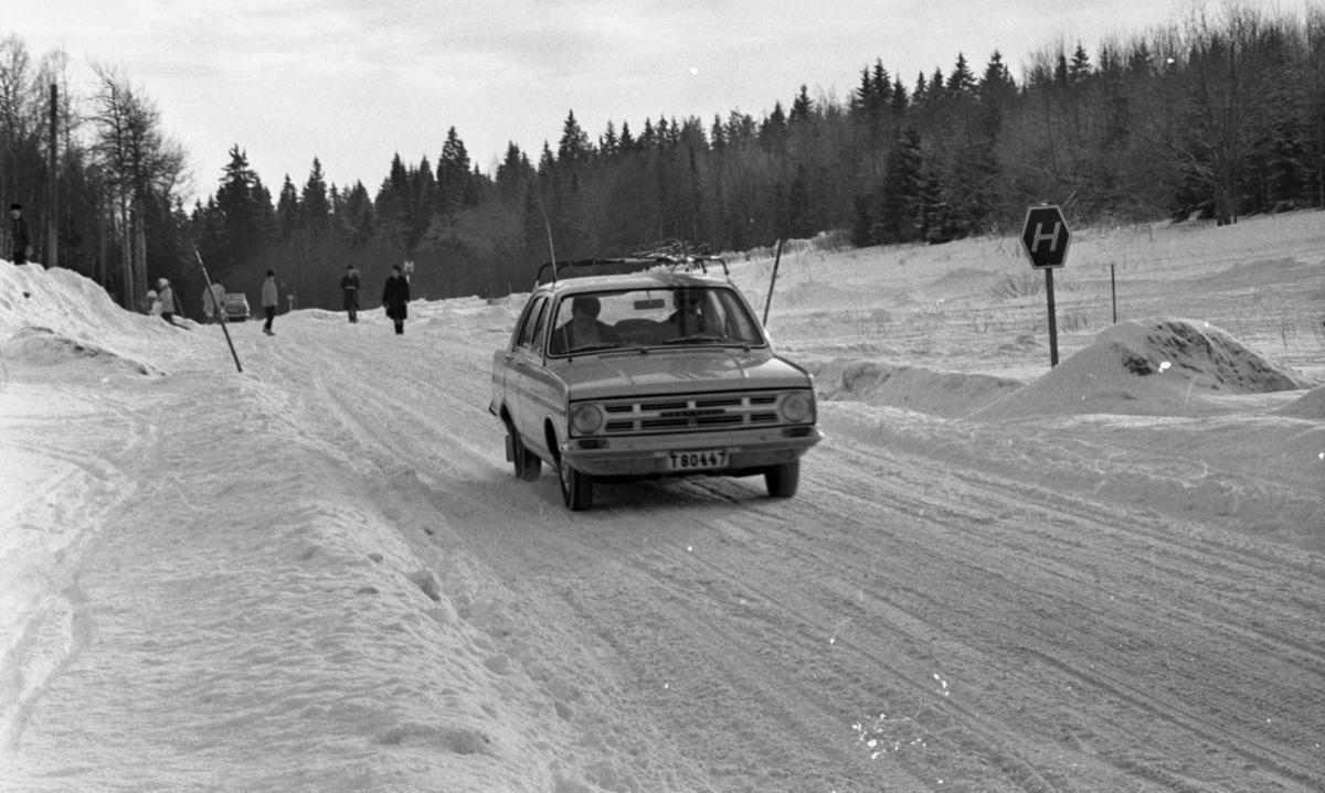 Ånnaboda 29 januari 1968En bil kommer körande på en väg i Ånnaboda. Marken är täckt av snö. Människor syns i bakgrunden.
