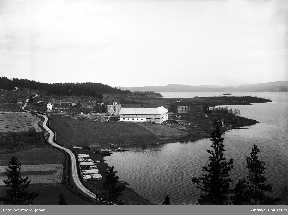 Byggnationen av sjukhemmet/fattigvårdsinrättningen i Öjestrand, Njurunda. Närmast ses ladugården. Byggnaden vid vattnet är barnhem. På platsen fanns tidigare Svala fattiggård som brann ner 1911.