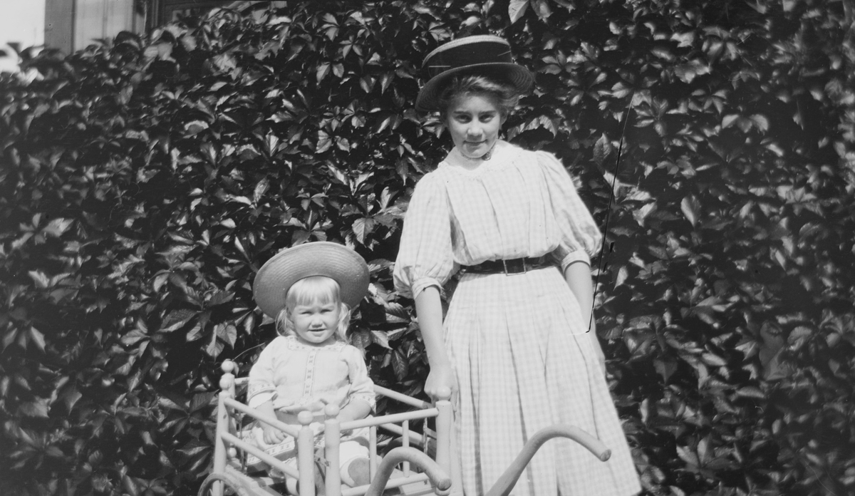 Iacob Ihlen Mathiesen sitter i en lekekjerre, søstera Celina Marie står ved siden av foran en vegg av eføy.