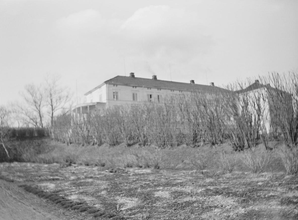 Hovedbygningen på Linderud Gård skimtes gjennom og bak klipte hekker og trær uten løv.