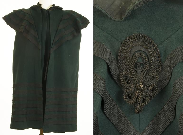 Kort kåpe eller cape med hette, brede slag og sorte dekorbånd på slag og nederst.