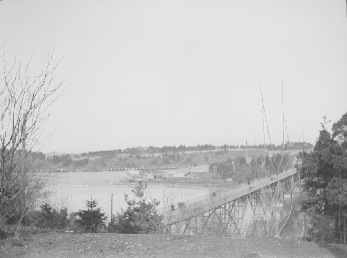 Det går en bro med buede jernkonstruksjoner over en bred elv eller fjordarm eller lignende. Flere mennesker går på broen. I front sees trær uten løv samt nåletrær, det er bratt ned til vannet. I bakgrunnen sees en lav ås med trær og bebyggelse.