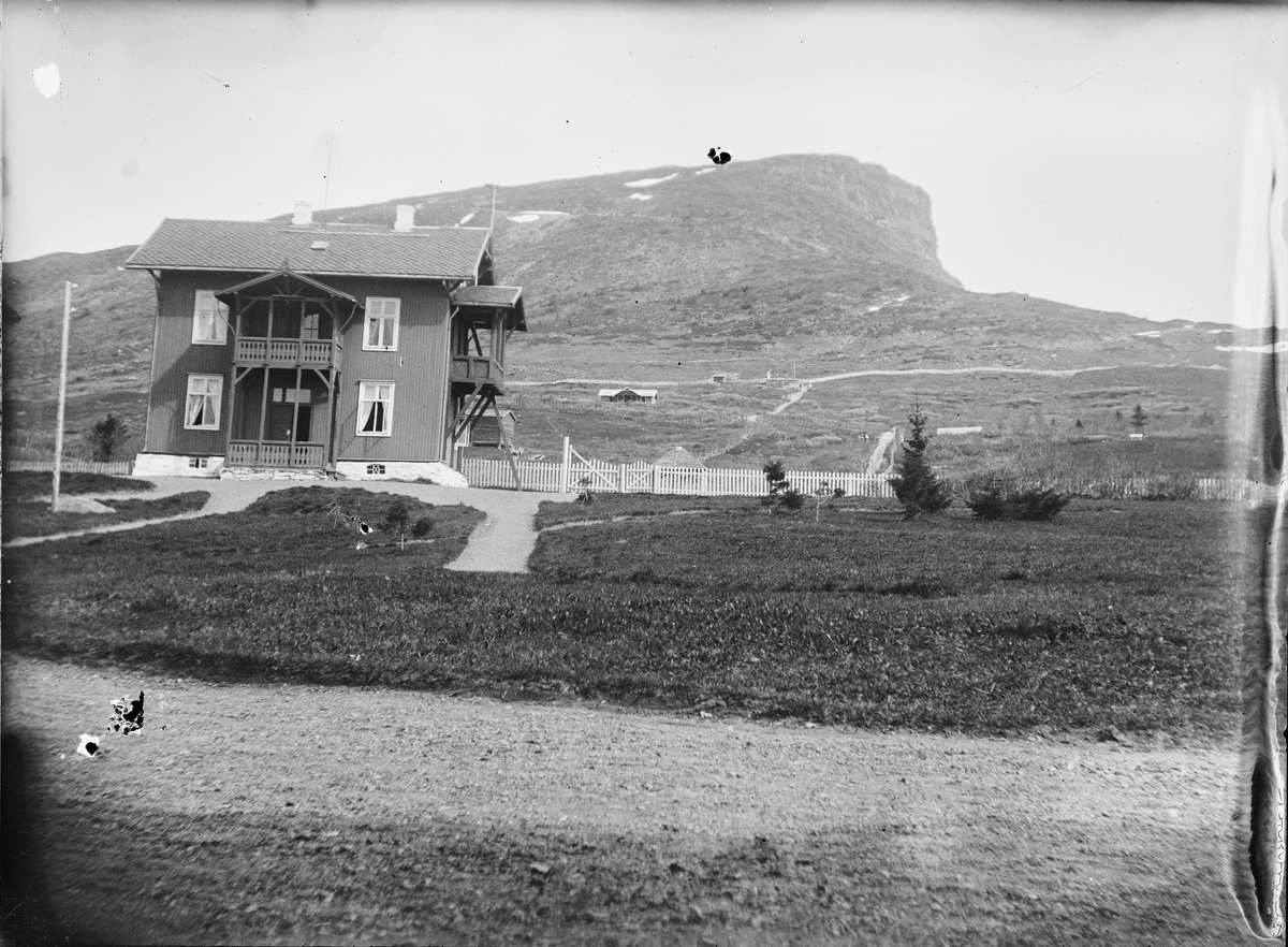 Et toetasjes hus med inngjerdet hage. Huset er bygget i et fjellandskap hvor en ser lave hytter. I bakgrunnen, Skeikampen.